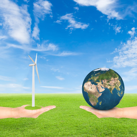 Green Earth concept,hand holding wind turbine and earth against green field and blue sky background.