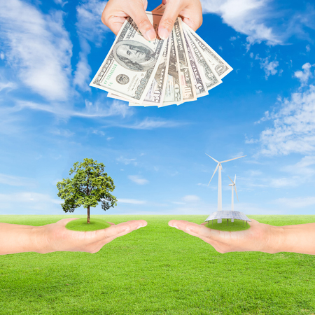 Carbon credits concept,hand holding wind turbine, solar panels, tree and US Dollars banknote against green field and blue sky background photo