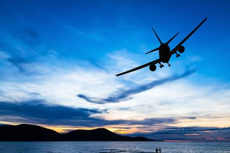 silhouetted: Silhouetted commercial airplane flying above the sea at sunset Stock Photo