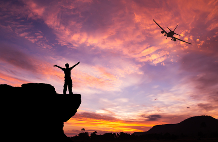 adventure sports: Silhouette of a man on the rock and silhouette commercial plane flying at sunset Stock Photo