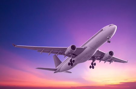 Commercial airplane flying at sunset Stock Photo