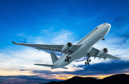 commercial vehicle: Commercial airplane flying at sunset Stock Photo