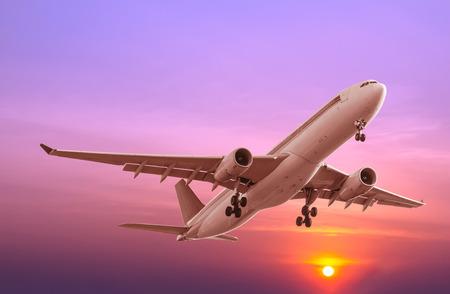 Avion commercial volant au coucher du soleil