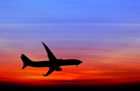 silhouetted: Silhouetted commercial airplane flying at sunset