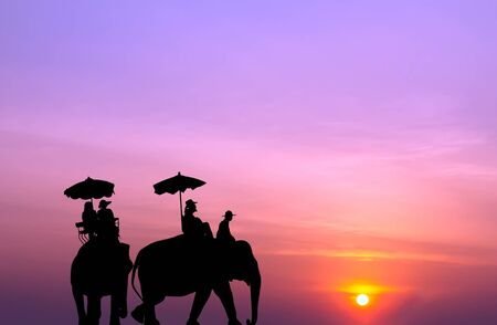 mahout: silhouette elephant with tourist at sunset