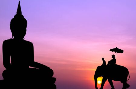 mahout: silhouette elephant with tourist in front of big buddha at sunset Stock Photo