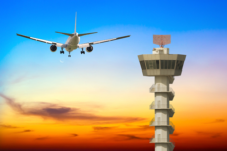 airplane take off: Commercial airplane take off over airport control tower at sunset