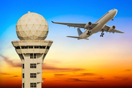 control tower: Commercial airplane take off over airport control tower at sunset