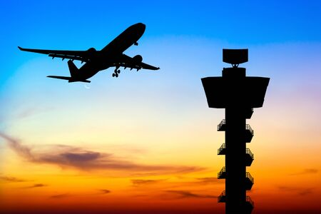 control tower: Silhouette commercial airplane take off over airport control tower at sunset Stock Photo