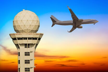control tower: Commercial airplane flying over airport control tower at sunset