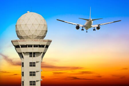 torre di controllo: Commercial airplane take off over airport control tower at sunset