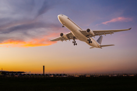 Commercial airplane take off at sunset Stock Photo