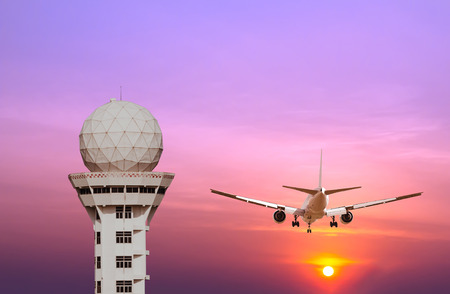 airplane landing: Airport control tower and commercial airplane landing at sunset Stock Photo