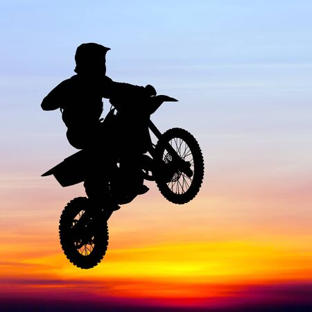 motorcross: silhouette of motocross rider jump in the sky at sunset Stock Photo
