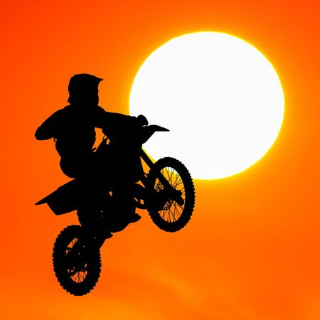 silhouette of motocross rider jump in the sky at sunset Stock Photo