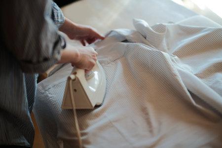 woman ironing shirt at home