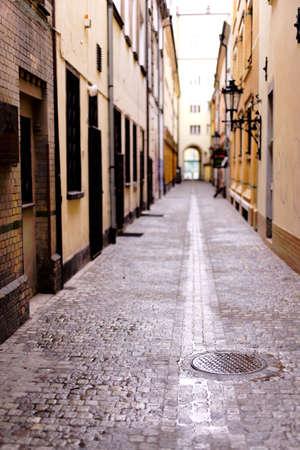 housing style: Narrow, wet cobbled street Stock Photo
