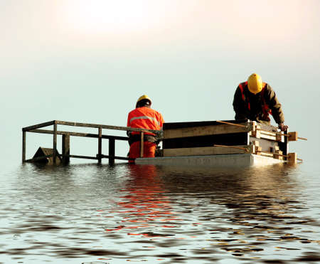 submerged: Two builders on huge submerged  pillar