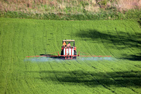 farm tractor spraying field before planting photo