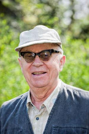 hombre sentado: Hombre mayor feliz que se sienta en el parque Foto de archivo