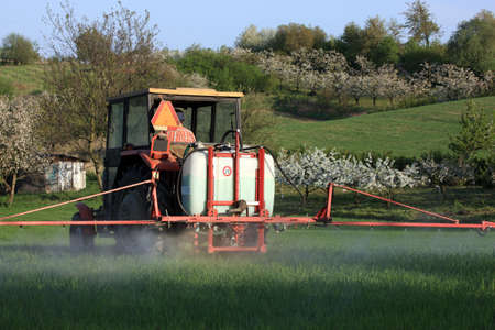 dolnoslaskie: farm tractor spraying field before planting Stock Photo