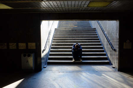 Lonely man sitting on the stairs Stock Photo