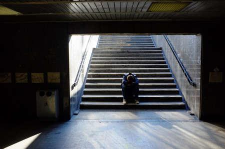 Merdivenlerde oturan yalnız bir adam Stock Photo