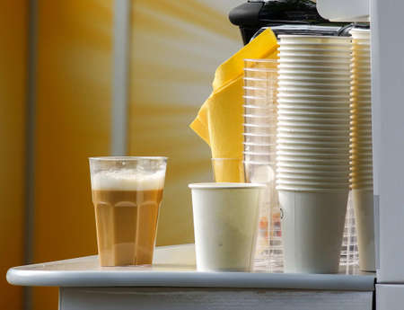 Plastic cups and glass full of beverage lying on the table Stock Photo