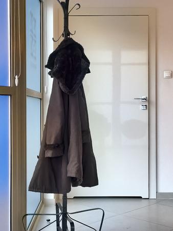 Men's coat hanging in empty office 版權商用圖片