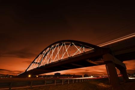 denver skyline at sunset: An orange sky provides the backdrop as a light rail train passes over an lighted truss bridge   Denver, Colorado  Stock Photo