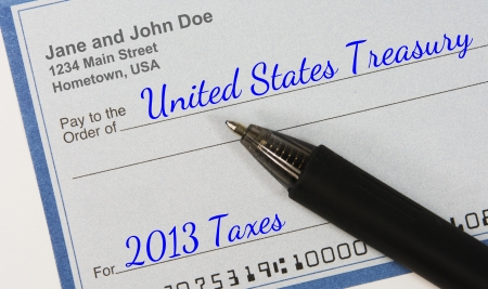A personal check with pen, made payable to the United States Treasury for 2013 Taxes Stock Photo - 25361611