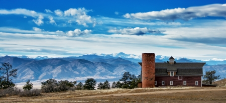 mount evans: A red barn perched on a tall ridge looks over the front range of the Colorado Rocky Mountains south of Denver  The first snowfalls have covered Mount Evans  a 14,000 ft  peak  and the Indian peaks in the distance  Editorial
