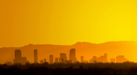 denver skyline with mountains: A bright and hazy orange sunset silhouettes the Denver, Colorado skyline against the Foothills of the Rocky Mountains   Stock Photo