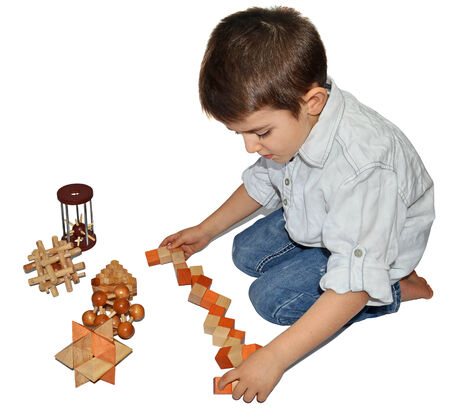 Boy with many wooden logic toys