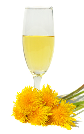 nature cure: Dandelion wine in glass on a white background