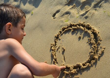 sand drawing: Kid drawing in the sand Stock Photo