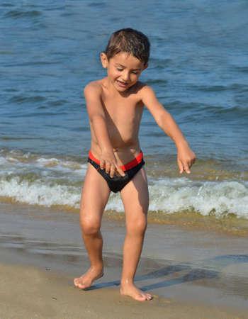joyous: Kid dancing joyous on the beach Stock Photo