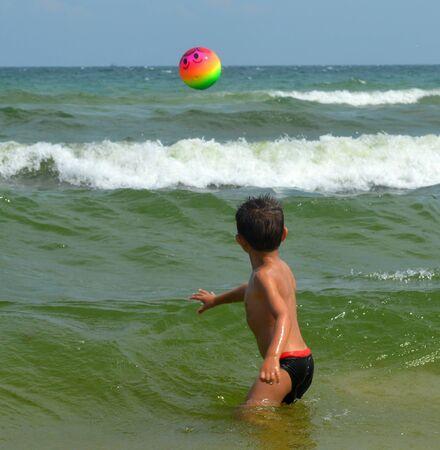 throws: Kid throws a ball in sea