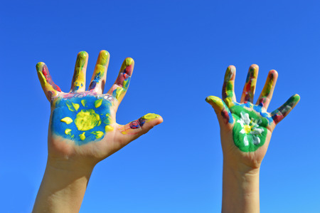 kids painted hands: Painted kid hands on a blue sky background