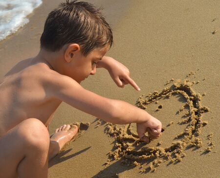 sand drawing: Kid drawing in the sand at the beach Stock Photo