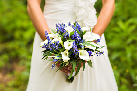 Bride Holding Wedding Bouquet with beautiful Flowers Stock Photo
