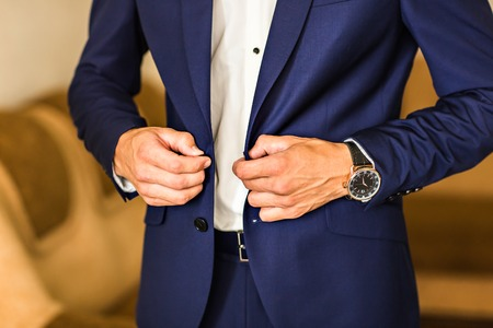 buttoning: Making business look good. Close-up of man buttoning his jacket while standing against grey background