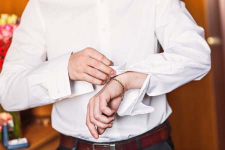 cuff link: A groom putting on cuff-links as he gets dressed in formal wear .Grooms suit