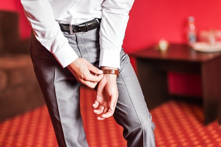 businesswear: A groom putting on cuff-links as he gets dressed in formal wear .Grooms suit