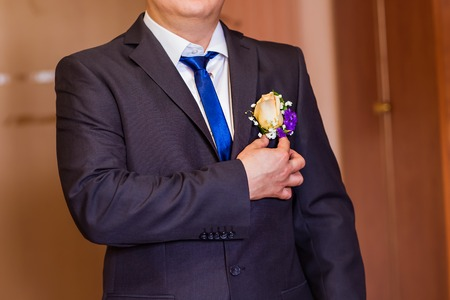 suit  cuff: A groom putting on cuff-links as he gets dressed in formal wear .Grooms suit