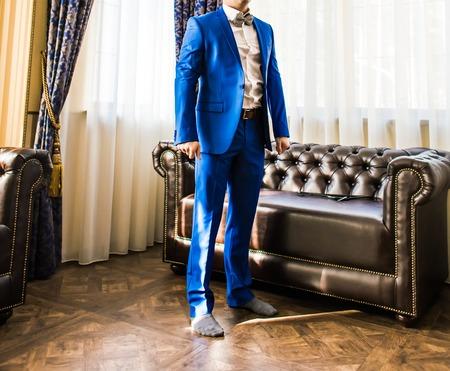 Un novio que pone en gemelos como él se viste con ropa formal traje de .Groom