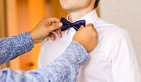 cuff links: A groom putting on cuff-links as he gets dressed in formal wear .Grooms suit