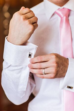 A groom putting on cuff-links as he gets dressed in formal wear .Grooms suit