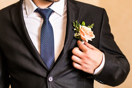 Posed groom with rose button hole.Wedding details, beautiful boutonniere, men's details
