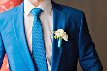 Posed groom with rose button hole.Wedding details, beautiful boutonniere, men's details 版權商用圖片 - 42446866